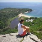 Reflective Thinker: woman sitting on a boulder overlooking a peninsula